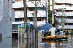 Mężczyzna wiosłuje jego bambusową tratwę za telefonu budka w zalewającej ulicie Bangkok, Tajlandia, na 06 2011 Listopadzie Fotografia Royalty Free