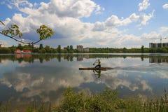 Mężczyzna wiosłuje na kajak łodzi na miasta jeziorze Zdjęcia Royalty Free