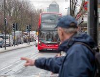 Mężczyzna wita Londyńskiego czerwonego autobus Canary Wharf w tle fotografia royalty free