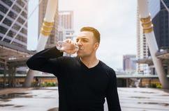 Mężczyzna woda pitna po biegać ćwiczenie przy miastem fotografia royalty free