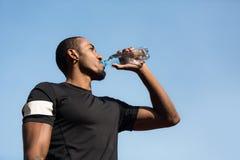 Mężczyzna woda pitna po biegać i odpoczywać obraz stock