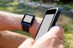 Mężczyzna wręcza być ubranym mądrze zegarek i używać telefon komórkowego Zdjęcie Royalty Free