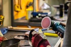 Mężczyzna wręcza częstowanie metalu części narzędzia w warsztacie z fotografia royalty free