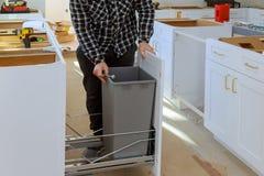 Mężczyzna wręcza gromadzić meblarskiego śmieciarskiego kosz w kuchni zdjęcia stock