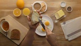 Mężczyzna wręcza narządzaniu śniadaniową grzankę z masłem, odgórny widok zbiory