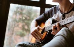 Mężczyzna wręcza obsiadanie na dużym nadokiennym windowsil i bawić się na gitarze - palce zamykają w górę wizerunku zdjęcie royalty free