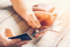 Mężczyzna Wręcza trzymać kredytową kartę i używać telefon komórkowego w świetle słonecznym Zdjęcie Stock