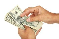 Mężczyzna wręczają mieniu sto dolarów rachunku na białym tle Zdjęcia Stock