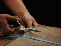 Mężczyzna Wręczają Rżniętą tkaninę na ciemnym tle Nożyce w męskich rękach przyrząd zamierzająca długości miara pomiaru taśmy Mier Zdjęcie Royalty Free