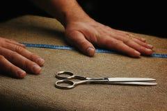 Mężczyzna Wręczają Rżniętą tkaninę na ciemnym tle Nożyce w męskich rękach przyrząd zamierzająca długości miara pomiaru taśmy Mier Fotografia Royalty Free