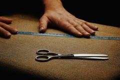 Mężczyzna Wręczają Rżniętą tkaninę na ciemnym tle Nożyce w męskich rękach przyrząd zamierzająca długości miara pomiaru taśmy Mier Fotografia Stock