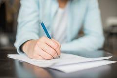 Mężczyzna writing przy biurkiem Zdjęcia Royalty Free
