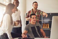 Mężczyzna wskazuje przy komputerem obok pracowników zdjęcie stock