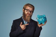 Mężczyzna wskazuje przy nim z ręka palcem wskazującym z Piggybank Z Eyeglasses obrazy stock