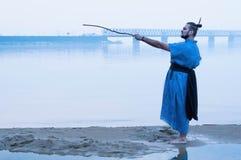 Mężczyzna wskazuje z drewnianym kijem przy niebem w błękitnym kimonie na brzeg rzekim w mgle obrazy royalty free