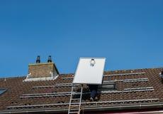 Mężczyzna wspina się drabinę z panelem słonecznym Obraz Royalty Free