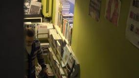 Mężczyzna wspina się schodki Multicam, nowożytna przestrzeń, bookstore, biblioteka zbiory