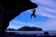 Mężczyzna wspina się skały na plaży Obraz Royalty Free