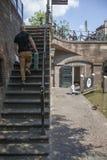 Mężczyzna wspinaczki drylują schodki przy kanałowym oudegracht w średniowiecznym mieście Utrecht podczas gdy inny mężczyzna odpoc obraz stock