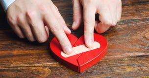 Mężczyzna wtyka wpólnie czerwonego serce z tynkiem Odnowienie związek Rodzinne psychoterapeuta usługi pojednanie zdjęcia stock