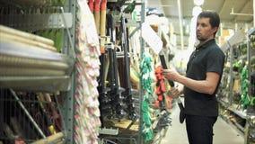Mężczyzna wybiera łopatę w narzędzia sklepie zdjęcie wideo