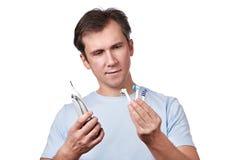 Mężczyzna wybiera changeable głowę dla elektrycznego toothbrush Obraz Stock