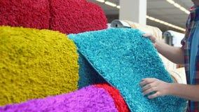 Mężczyzna wybiera dywan, zakończenie up zbiory wideo