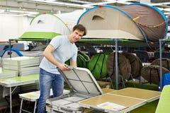 Mężczyzna wybiera falcowanie obozu stół w sklepu czasu wolnego towarach zdjęcia royalty free