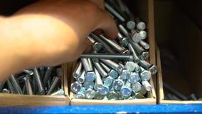 Mężczyzna wybiera metali rygle i części męska ręka, buduje sklep, rygle zdjęcie wideo