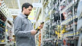 Mężczyzna wybiera nastawczego spanner w narzędzia sklepie zbiory