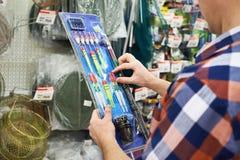 Mężczyzna wybiera pławiki dla łowić w sklepie fotografia royalty free