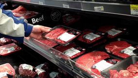 Mężczyzna wybiera surową wołowinę w sklepie spożywczym