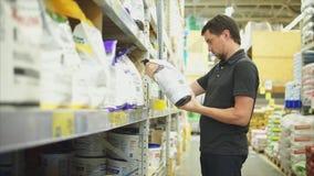 Mężczyzna wybiera torbę gipsowy tynk dla domowego odświeżania w narzędzia sklepie zdjęcie wideo