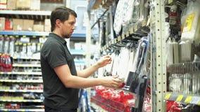 Mężczyzna wybiera towary w narzędzia dziale w centrum handlowym zdjęcie wideo