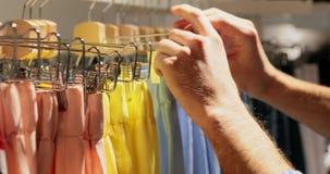 Mężczyzna wybiera zakup w kobieta sklepie odzieżowym zbiory