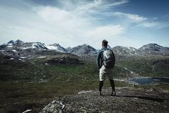 Mężczyzna wycieczkowicz z plecakiem na szczytowym wierzchołku cieszy się widok zdjęcia royalty free
