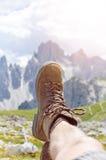 Mężczyzna wycieczkowicza kłamstwo na ziemi Szczyty jak tło słoneczny dzień Trekking buty Obiektywu raca Pomyślny backpacker ciesz Zdjęcia Royalty Free