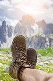 Mężczyzna wycieczkowicza kłamstwo na ziemi Szczyty jak tło słoneczny dzień Trekking buty Obiektywu raca Pomyślny backpacker ciesz Obraz Stock