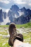 Mężczyzna wycieczkowicza kłamstwo na ziemi Szczyty jak tło słoneczny dzień Trekking buty Obiektywu raca Pomyślny backpacker ciesz Obrazy Royalty Free