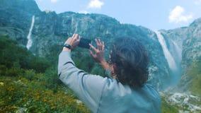 Mężczyzna wycieczkowicza podróżnika turysta fotografuje wysokie siklawy w górach na smartphone zakończeniu zdjęcia stock
