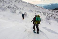 Mężczyzna wycieczkuje w zim górach przed burzą Obrazy Stock