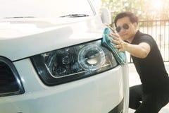Mężczyzna wyciera samochód z microfiber płótnem Utrzymanie szczegóły które skupiają się na reflektorach zdjęcie royalty free