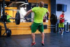Mężczyzna wykonuje barbell podchwyt przy gym zdjęcie royalty free