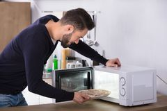 Mężczyzna Wypiekowa pizza W mikrofala piekarniku obraz stock