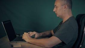 Mężczyzna wyszukuje internet przy laptopem Mężczyzna surfingu internet siedzi przy stołową opóźnionego wieczór nocą Studencki pat zbiory wideo