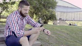 Mężczyzna wyszukuje smartphone, siedzi na schodkach Suwaka strzał, dobro zbiory