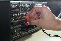 Mężczyzna złączony audio depeszuje na muzycznego amplifikatoru tylnym panelu Fotografia Royalty Free