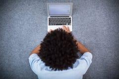 Mężczyzna z afro włosianym używa laptopem Fotografia Stock