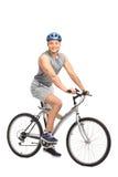 Mężczyzna z błękitnego hełma obsiadaniem na jego rowerze Zdjęcia Stock