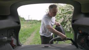 Mężczyzna z błękitnym hoover otwiera samochodowego bagażnika i zaczyna vacuuming zbiory
